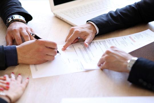 Signature d'un contrat de vente par un jeune couple