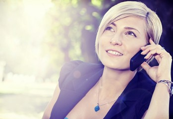 Smiling woman on the call outdoors