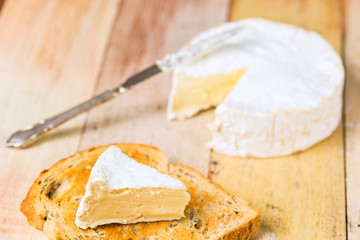 Camembert cheese with cut wedge on toasted bread slice and vinta