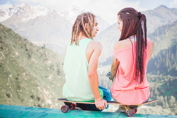 Couple of hipster, young people at mountain with longboard skateboard