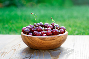 Wooden plate full with ripe red cherries