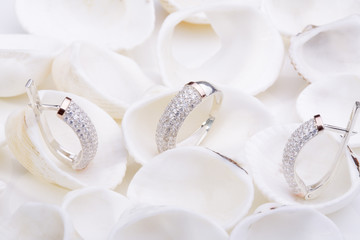 Beautiful gold ring and earrings with diamonds on white seashells.