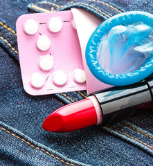 Closeup oral contraceptive pills, condom and red lipstick.