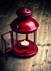 Лампа на деревянном полу в темноте,со светом свечи