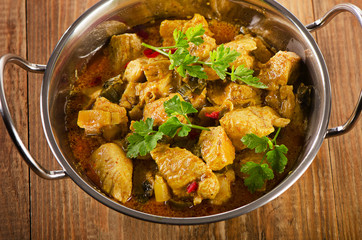 Chicken curry in  balti dish on a rustic wooden table.