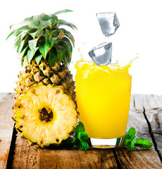Pineapple and ice with splash on wood