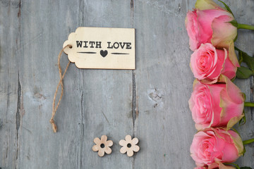 Row of pink yellow roses with label and heart shape decoration on a old wooden grey background
