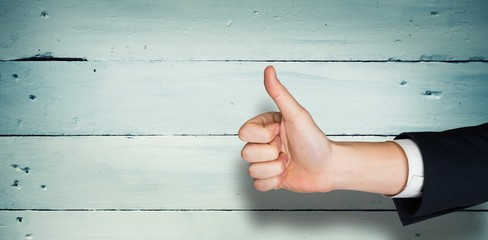 Composite image of hand showing thumbs up