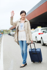 smiling young woman with travel bag over taxi