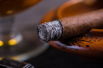 close view on cuban cigar with ash