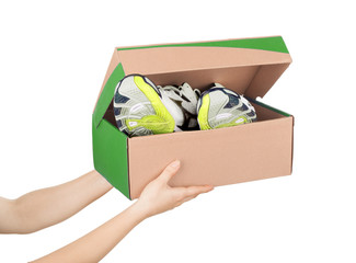 hands holding shoes in a box isolaterd on white background