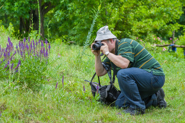 Enthusiastic mature photographer taking a photo of wild butterfly