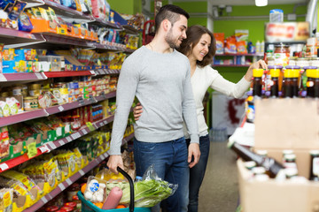 Adults buying canned food in shop