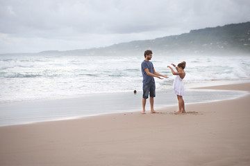 Father and daughter playing on the beach, Barbados