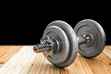 a dumbbell is on the wooden floor in a gym