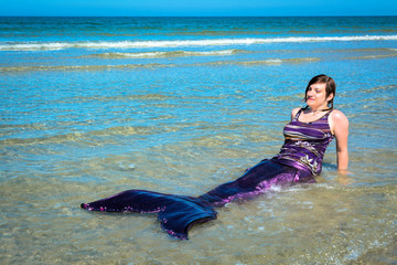 Frau im Meerjungfraukostüm am Strand