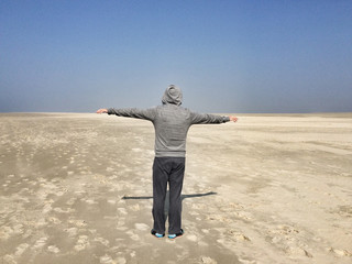 Rear view of a man with outstretched arms on a beach, Denmark