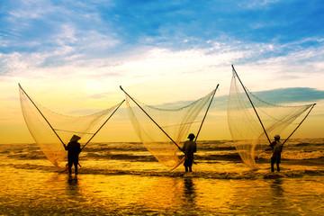 Fishermen fishing in the sea at sunrise in Namdinh, Vietnam.