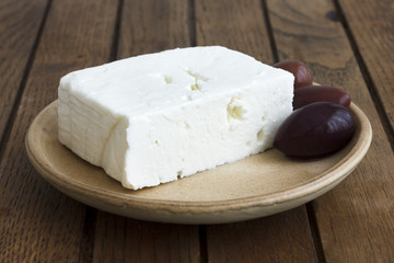 Greek feta cheese with kalamata olives on rustic plate and table