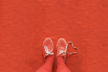 Knees down view of a woman's legs with a heart made out her shoelaces