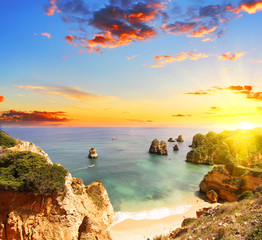 Rocky beach at sunset, Lagos, Portugal. Counter light. Travel and business background