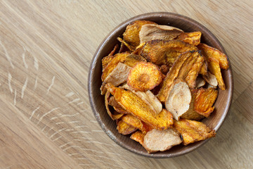 Fried carrot and parsnip chips in rustic wood bowl. From above.