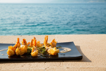 Serving plate with crispy shrimps and salad/Colorful dishware with seafood and vegetables