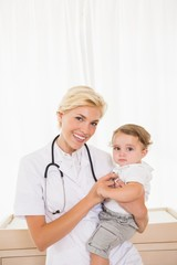 Portrait of a smiling blonde doctor and child