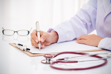 doctor writing record on folder on desk in office