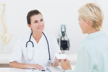 Patient giving cheque to her doctor