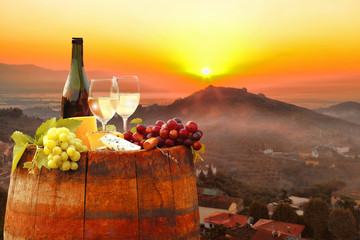 Wall Mural - White wine with barrel against colorful sunset in Chianti, Tuscany, Italy