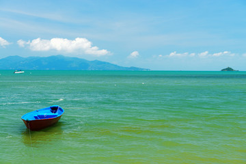 A small wooden boat moored on a beach in Thailand