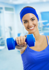 woman in sportswear doing fitness exercises with dumbbell