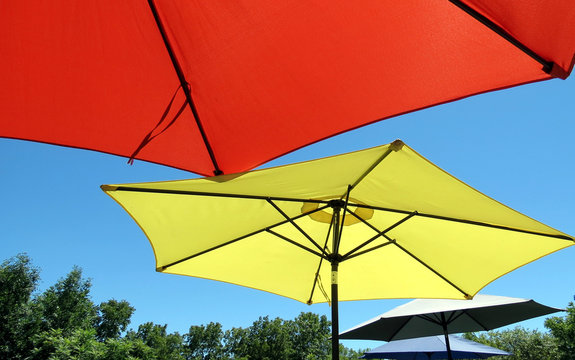 Large sun umbrellas shade patio picnic tables.