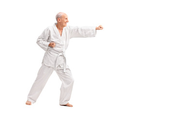 Old man in a white kimono practicing karate