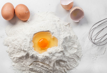 white background with egg in flour