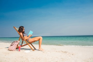 Pretty brunette reading a book on deck chair