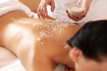 Spa Woman. Brunette Getting a Salt Scrub Beauty Treatment in Salon