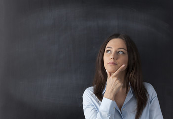 Thoughtful young woman on chalkboard background