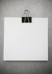 note paper and clip at metal background