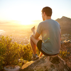 Young guy eating a protein bar at sunrise on a hike