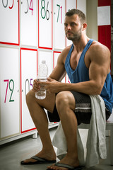 Man drinking water in locker room