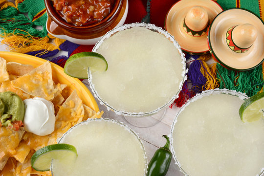 Margaritas: High angle view of three margarita cocktails surrounded by nachos, chips and salsa on a bright Mexican, table cloth. Horizontal format. Perfect for Cinco de Mayo projects.