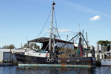 Black Fishing Boat Side - Rusty Black Fishing Boat with Tall Mast and Life Preservers Floating in Water at a Dock in Tarpon Springs Florida.