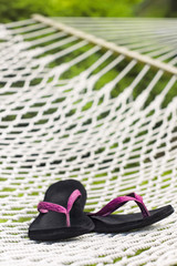 Pink flip flops on backyard rope hammock relaxing relaxation leisure concept