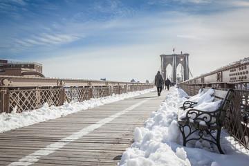 Brooklyn Bridge bench covered in Snow during winter season, New York