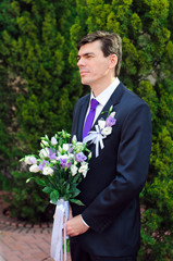 The groom with a bouquet in hand