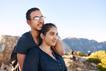 Young loving Indian couple in nature looking away optimistically