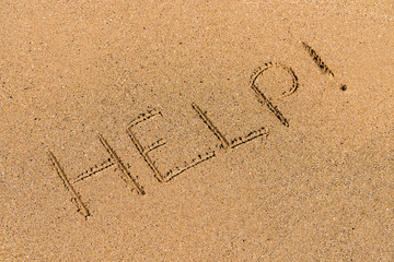Help Sign Drawn On Beach Sand