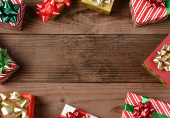 A high angle view of a group of Christmas presents on a rustic wooden floor. The presents are scattered around the edges of the frame leaving an empty middle for your object or copy.